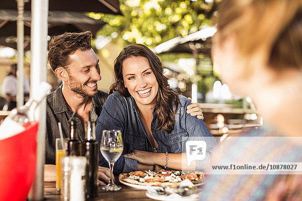 Couple at sidewalk cafe smiling