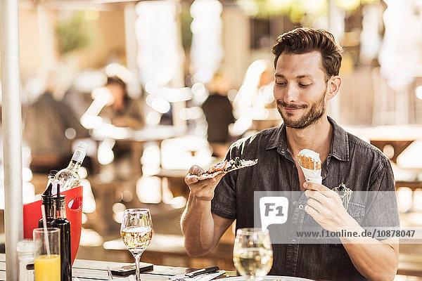 Mann am Straßencafé mit Eiswaffel und Pizzastück Mann am Straßencafé mit Eiswaffel und Pizzastück