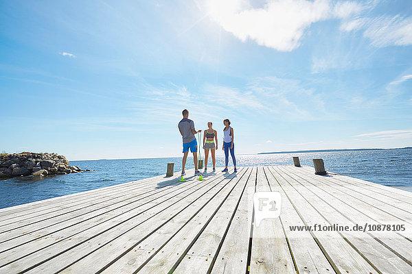 Mitteldistanzansicht von Freunden in Sportkleidung  die am Pier stehen