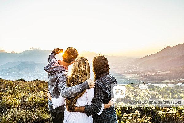 Rückansicht von Freunden am Berghang beim Selbstmord