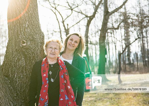 Erwachsene Tochter steht hinter der Mutter am Baum und schaut lächelnd in die Kamera