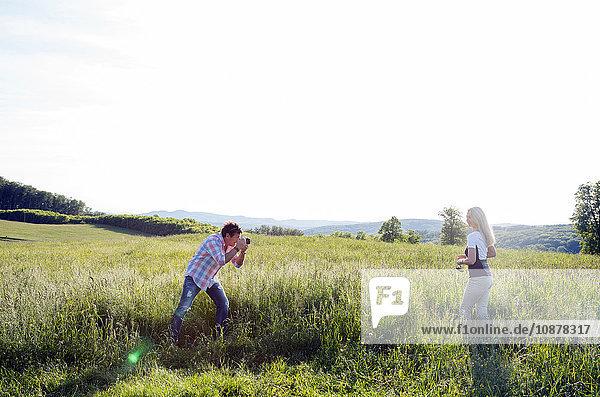 Mann fotografiert Frau im Feld