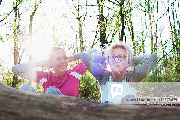 Women in forest hands behind head doing sit up against fallen tree