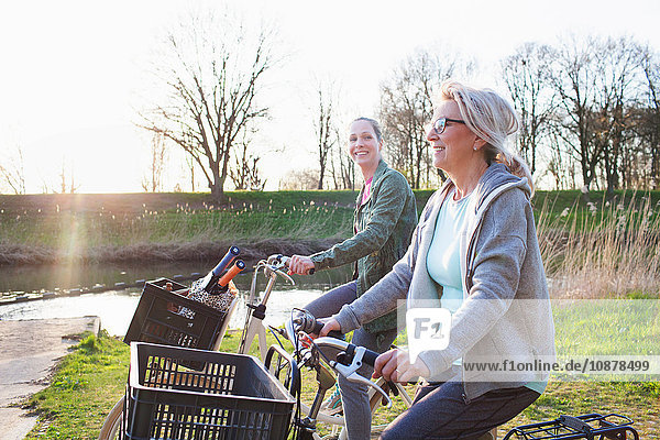 Side view of women cycling bicycles by river