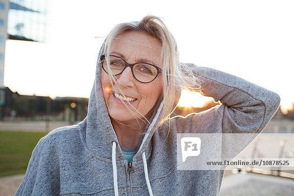 Porträt einer Frau mit Brille und Kapuzenoberteil  die lächelnd in die Kamera schaut