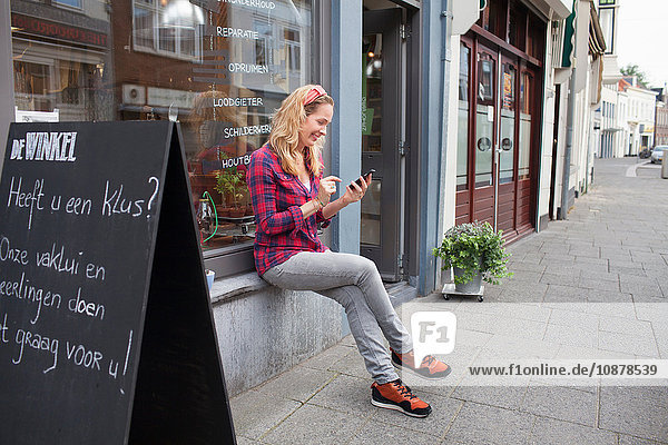 Woman sitting on shop windowsill looking down at smartphone smiling