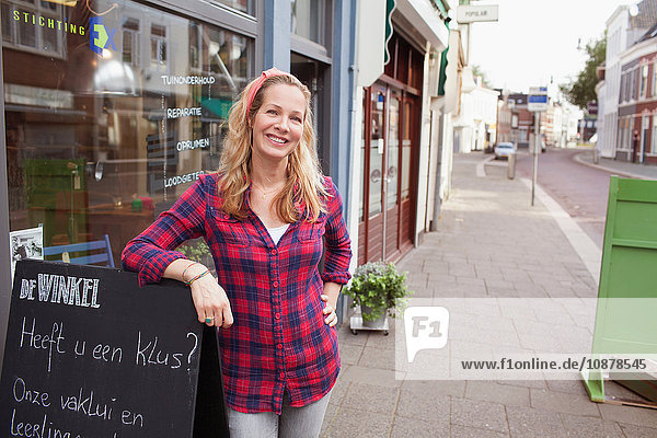 Woman in front of shop leaning against a-frame looking at camera smiling
