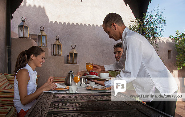 Waiter serving young couple breakfast  Marrakesh  Morocco