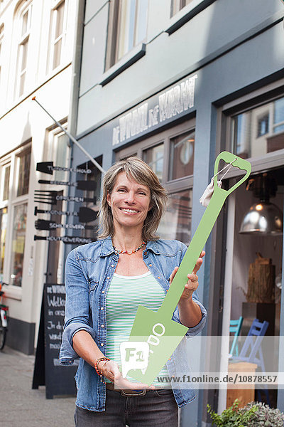 Woman in front of shop holding open sign looking at camera smiling