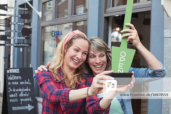 Women in front of shop holding open sign taking selfie with smartphone