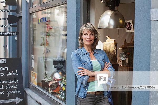 Woman in shop doorway  arms crossed looking at camera smiling