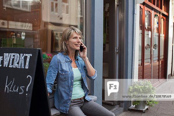 Woman sitting on shop windowsill making telephone call