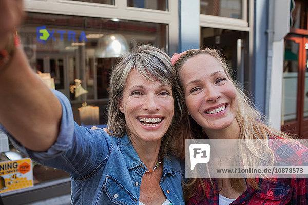 Women taking selfie looking at camera smiling