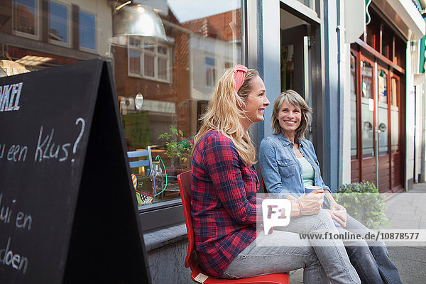 Women sitting on chairs in front of shop holding coffee cups smiling