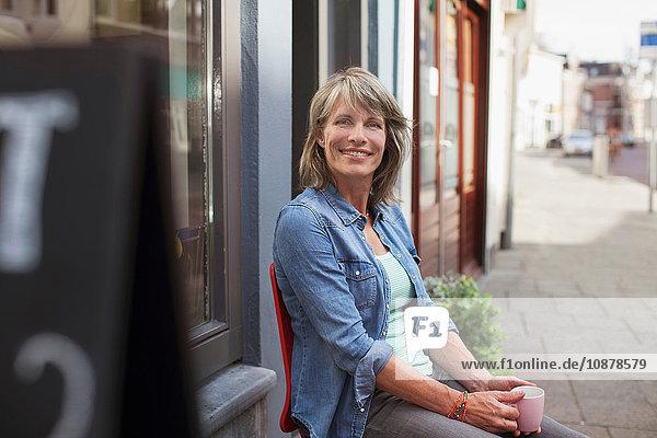 Frau sitzt auf einem Stuhl vor einem Geschäft und hält eine Kaffeetasse in der Hand und schaut lächelnd in die Kamera