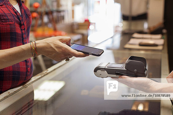 Cropped view of womans hands using smartphone to make contactless payment on smartphone