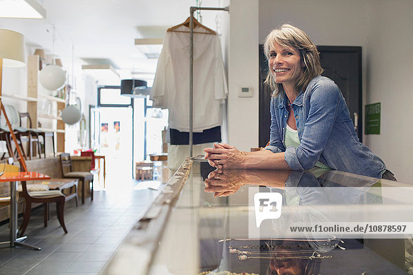 Shop assistant leaning against glass counter looking away smiling