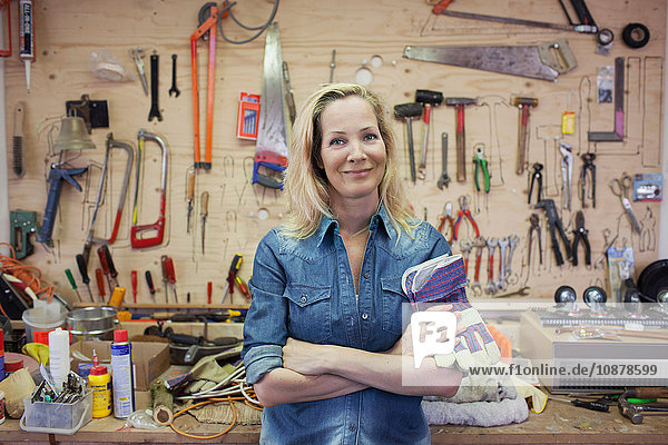 Woman in workshop  arms crossed holding protective gloves looking at camera smiling