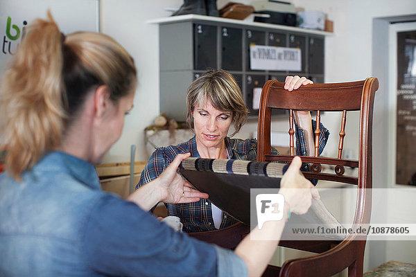 Women in workshop examining chair