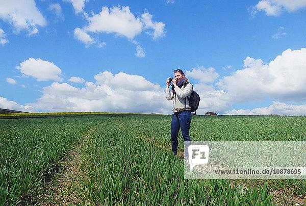 Junge Frau steht im Feld und fotografiert eine Landschaft