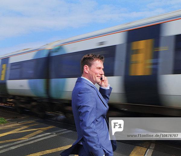 Geschäftsmann steht am Bahnübergang und benutzt ein Smartphone