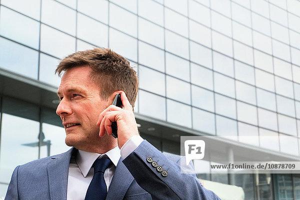 Reifer Geschäftsmann im Freien  der ein Smartphone benutzt