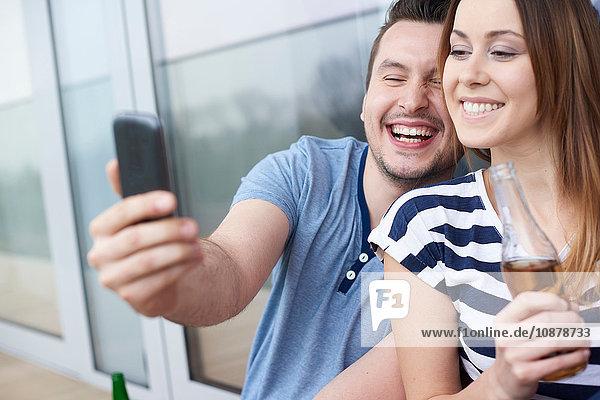 Junges Paar sitzt im Freien  macht ein Selbstporträt  benutzt ein Smartphone