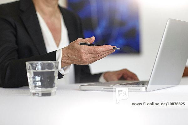 Ausschnitt einer Frau mit Laptop-Haltestift