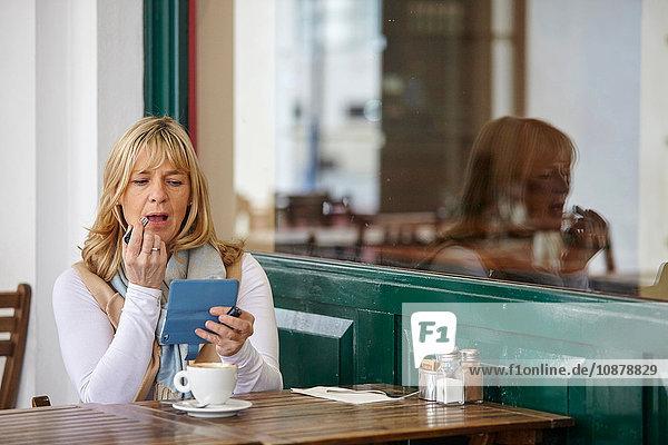 Reife Frau benutzt Smartphone zum Auftragen von Lippenstift am Tisch im Café auf dem Bürgersteig