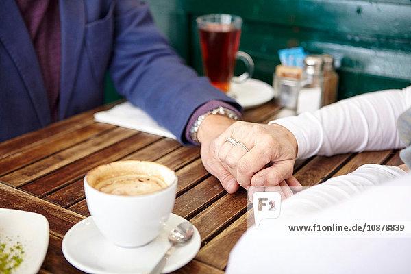 Nahaufnahme eines reifen Dating-Paares  das am Tisch eines Straßencafés Händchen hält