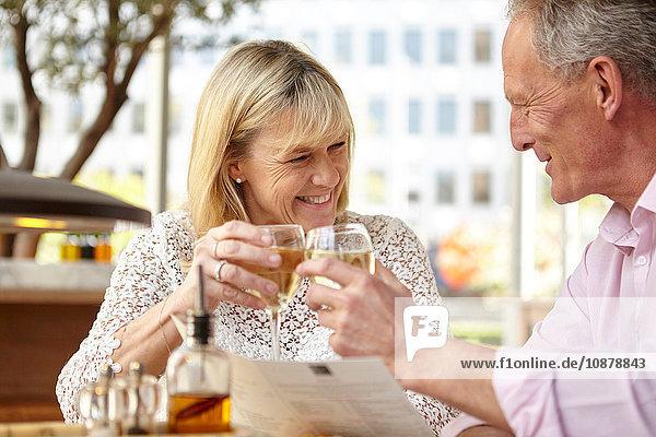 Reifes Dating-Paar  das am Restauranttisch ein Glas Weißwein trinkt