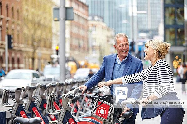 Reifes Dating-Paar beim Entfernen von Leihfahrrädern vom Gepäckträger  London  UK