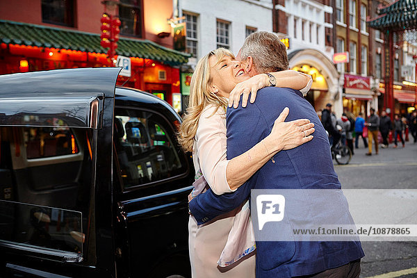 Mature dating couple hugging farewell in China Town  London  UK