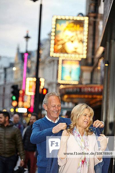 Ein reifer Mann zieht seiner Freundin in der Abenddämmerung auf der Straße in der Stadt die Jacke über die Schulter  London  Großbritannien