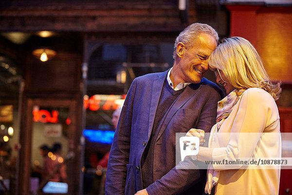 Reifes Dating-Paar mit Arm in Arm auf nächtlicher Straße in der Stadt  London  UK
