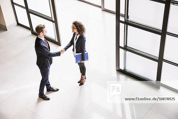 Schrägaufnahme einer Geschäftsfrau und eines Mannes  die sich am Eingang des Büros die Hand geben