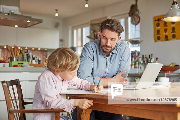 Father helping son with homework in home office