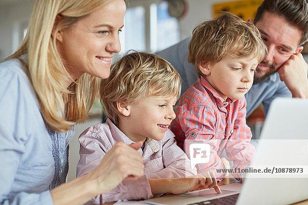 Eltern und Söhne mit Laptop
