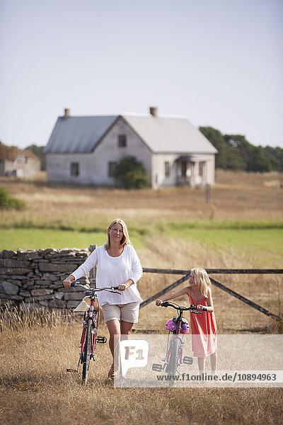Schweden,  Gotland,  Faro,  Mutter und Tochter (8-9) beim Radfahren auf dem Bauernhof