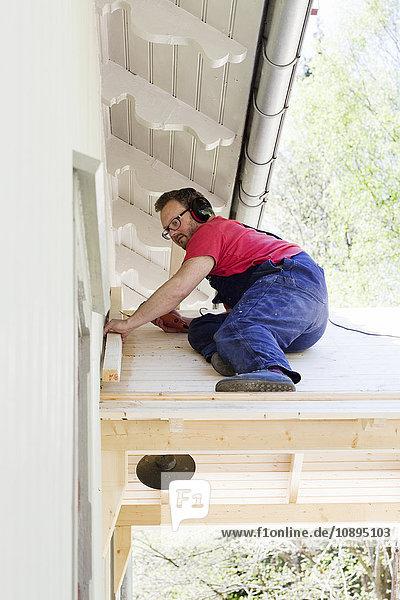 Schweden  Vastra Gotaland  Olofstorp  Hausbesitzer bei der Arbeit auf dem Hausdach
