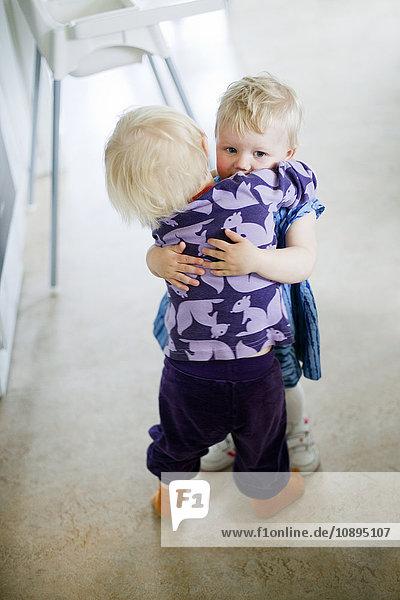Zwei Schwestern (2-3) umarmend