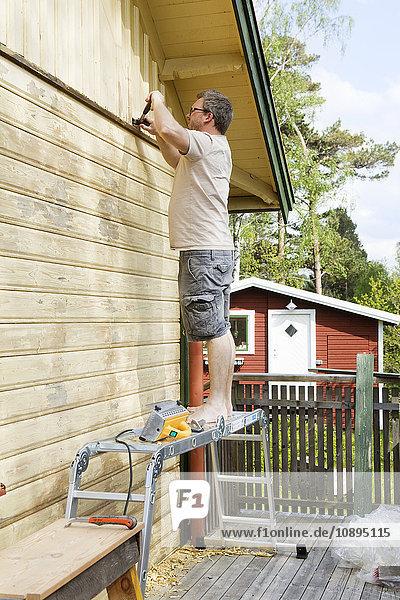 Schweden  Vastra Gotaland  Mittlerer Erwachsener Mann renoviert Hauswand