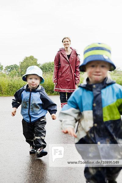 Schweden  Skane  Arild  Mutter und Töchter (2-3  4-5) auf nasser Straße unterwegs