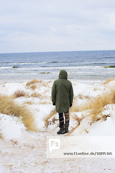 Sweden  Skane  Borrby  Rear view of mid adult man standing on beach in winter