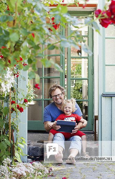 Schweden  Skane  Mossby  Porträt der Tochter mit Vater  der Tablett-PC hält