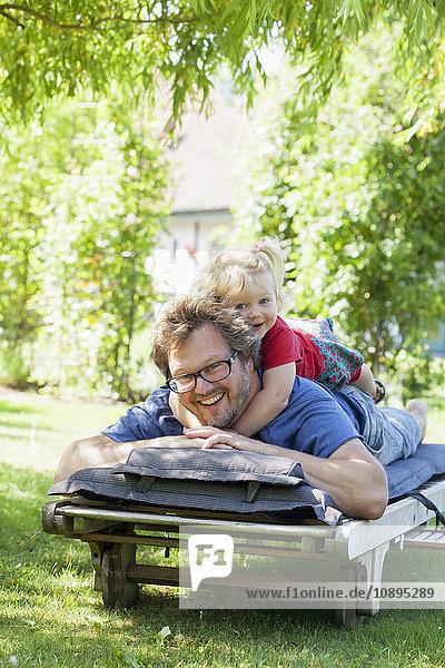 Schweden  Skane  Mossby  Portrait der Tochter mit Vater auf dem Liegestuhl liegend