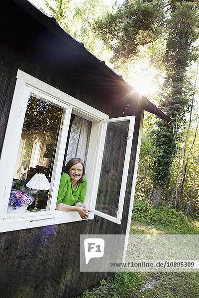 Schweden  Gotland  Frau schaut aus dem Fenster
