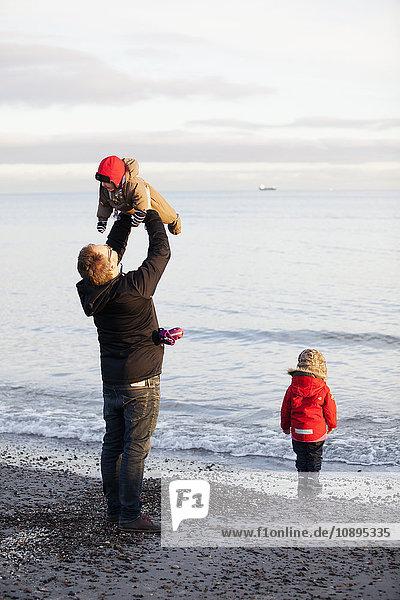 Dänemark  Grenen  Vater mit Töchtern (6-11 Monate) ( 2-3) spielen am Strand