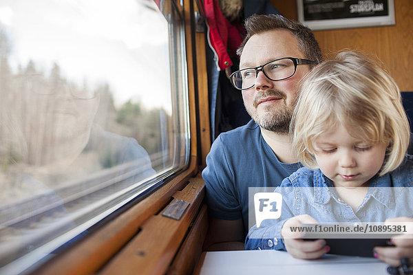 Schweden  Vater und Tochter (2-3) mit dem Zug unterwegs