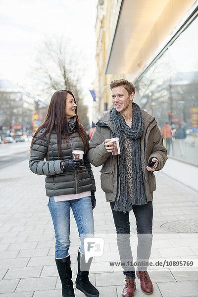 Schweden  Stockholm  Mann und Frau gehen auf der Straße und halten Kaffee in Einwegbechern.